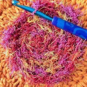 crocheting surface stitches of scrubby yarn to the center