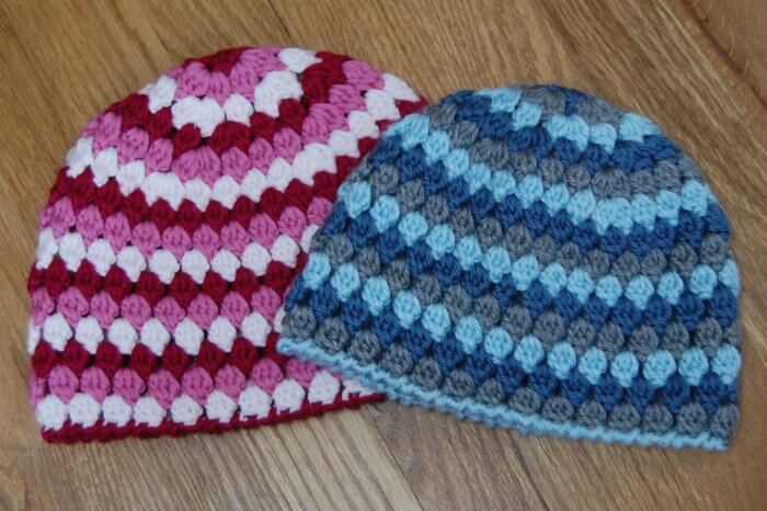 Three yarn colors are used to crochet both the child and the toddler hat sizes.
